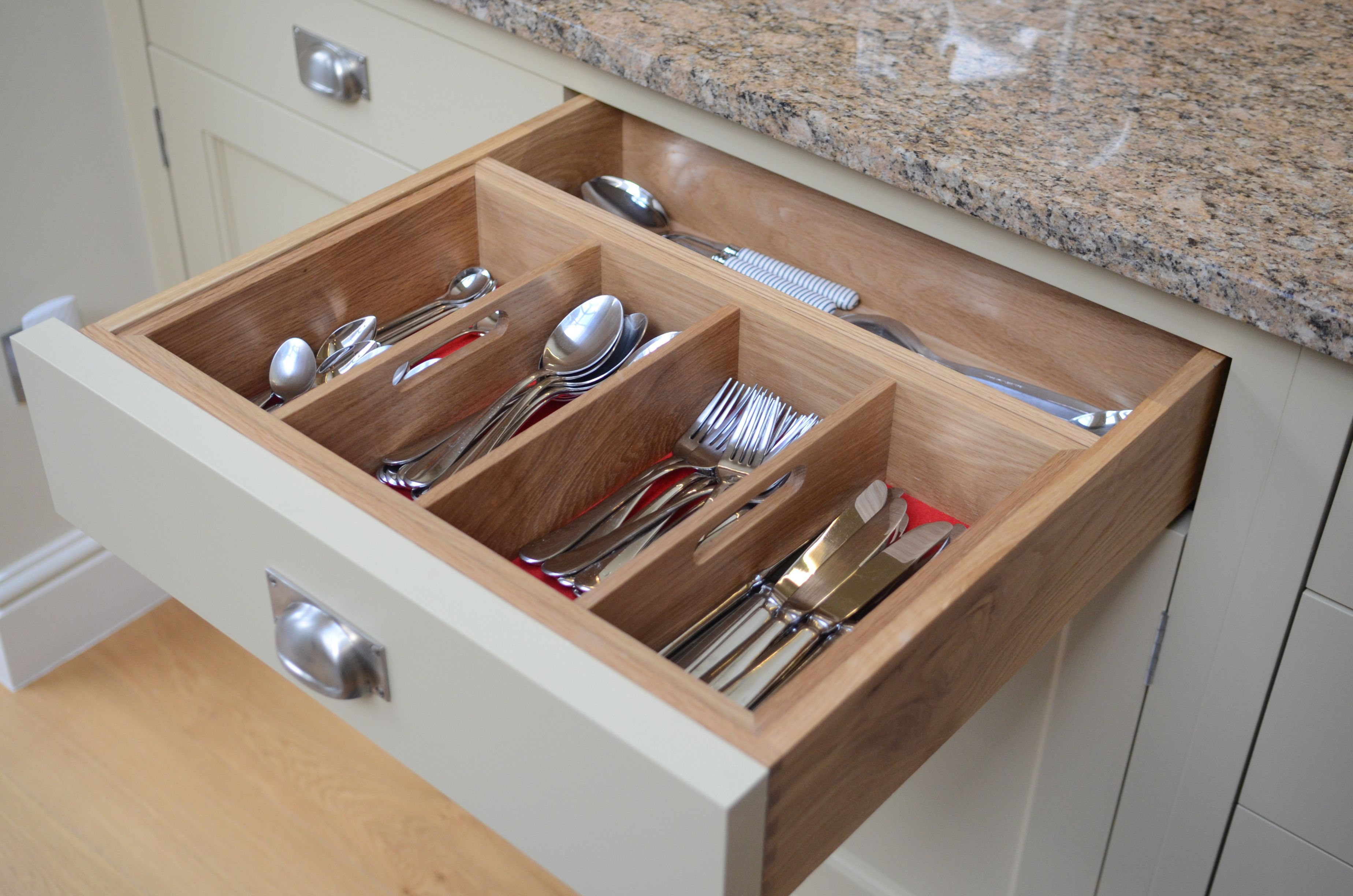 Oak cutlery drawer inserts with red felt bottom.  Cup handle on drawer.