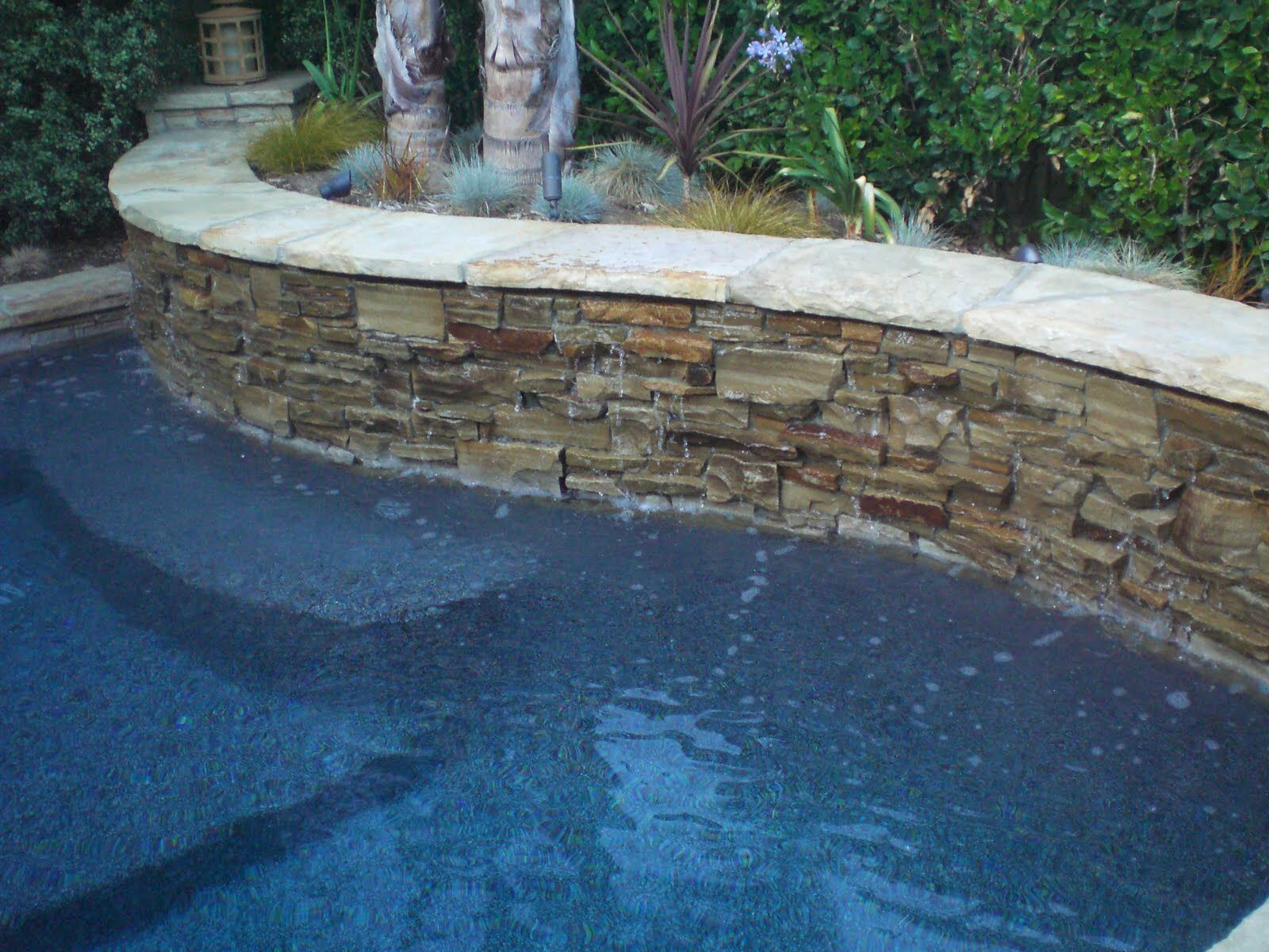 Pool With Stacked Stone Retaining Wall Stone Pool Pool Landscaping Backyard Pool