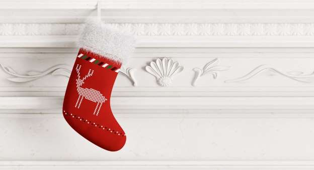 Red christmas stocking hanging on carved stone fireplace 3d rendering - Scovad/Getty Images