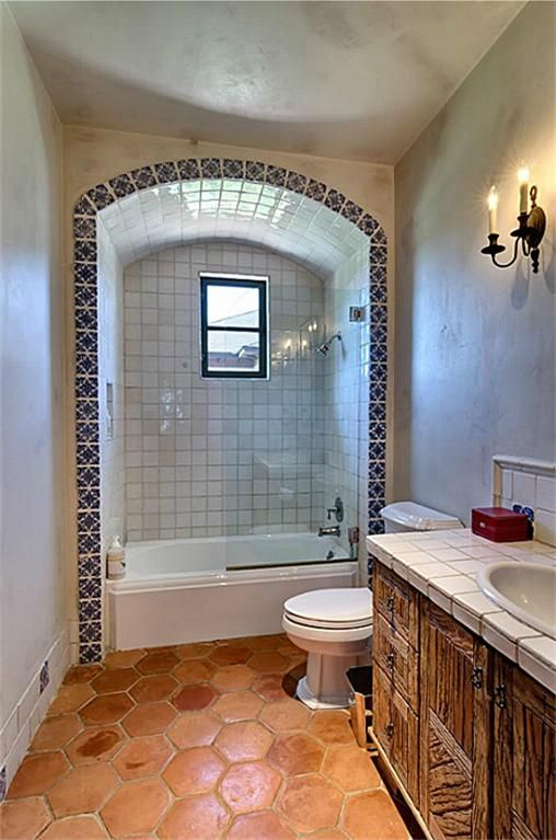 An Arched Alcove Edged With Artisan Tile Surrounds The Tub