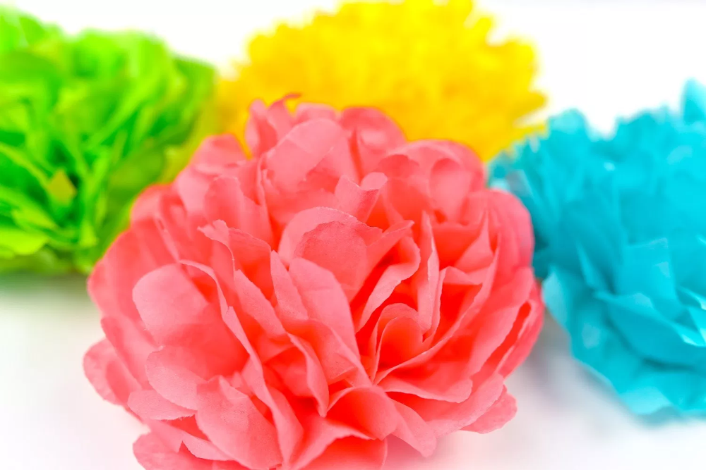 How to Make Tissue Paper Flowers Four Ways #paperflowerswedding Tissue paper flowers make a gorgeous event decor with a big impact—think weddings, baby showers, bridal showers and more! Learn how to make easy tissue paper flowers, as well as different methods for cutting the petals to create four unique styles. #easypaperflowers