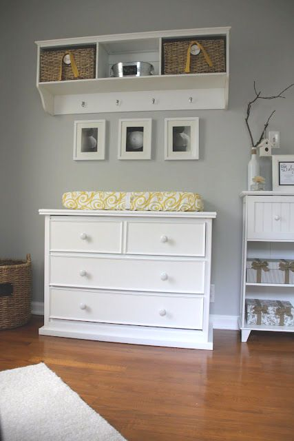 a white dresser and pottery barn lookalike wall storage system hold baby diapering items