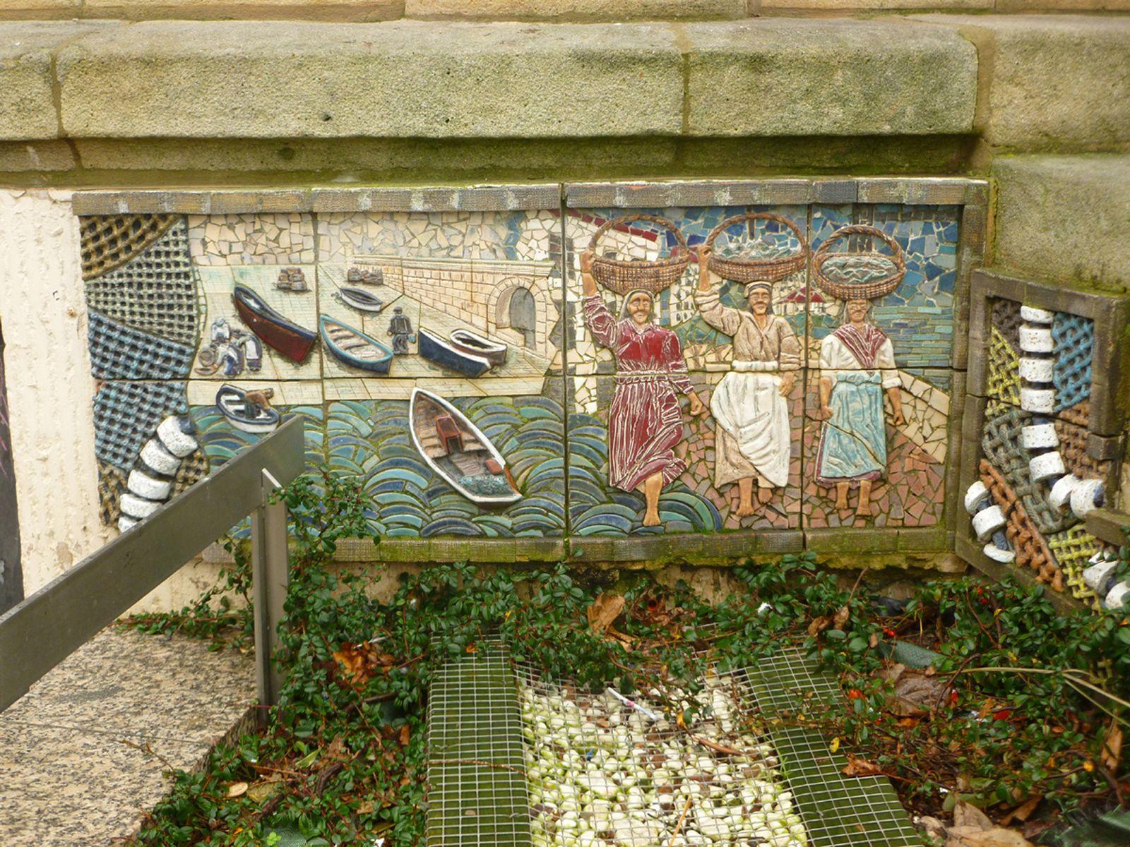 """""""LA SARDINERA"""". Mosaico rectangular en tesela cerámica modelado, en relieve,  por Paco Presa Merodio (Torrelavega, 1961 -). Instalado en 2007, fue realizado  en pasta de loza y arcilla roja y decorado con esmaltes y engobes coloreados, cocidos a 1050-1100º C. Rememora a la popular figura de la sardinera, representando: una vista de la rampa de los hombres en el puerto pesquero y tres sardineras descalzas con sus cestas a la cabeza, caminando por toda la orilla, como dice la canción."""