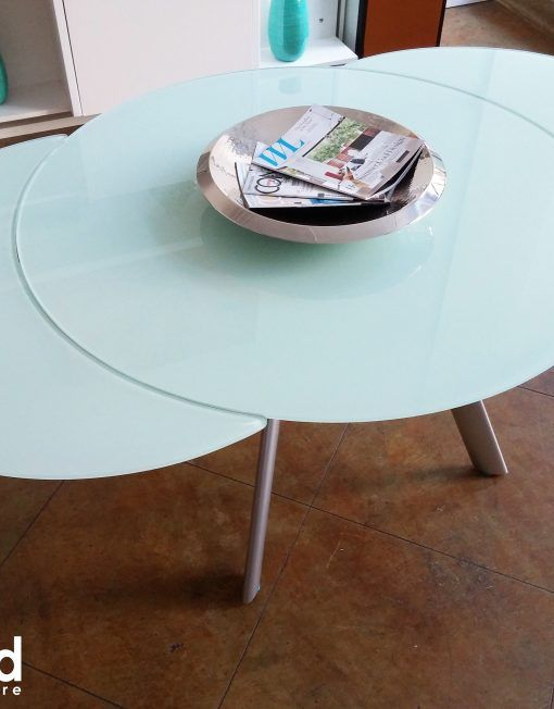 The Butterfly is a beautiful round glass dining table. It has two swiveling  sides which come out like butterfly wings in order to extend the table  length.