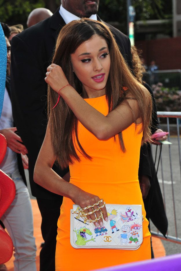 OMG SHE HAS A RUGRATS PURSE! And she's wearing all orange, like the old rugrats movie tapes that were all orange. Mad respect for this outfit lol | Ariana Grande With Her Hair Down Is Like An Entirely Different Person