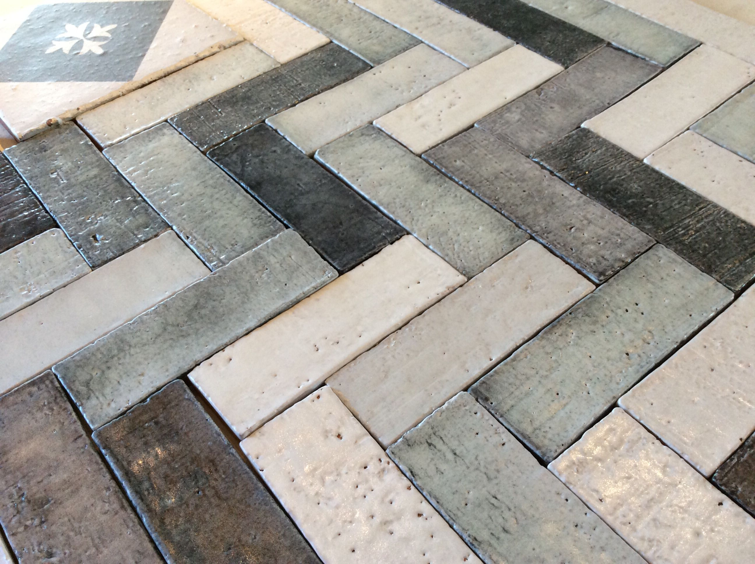Black, gray and white hand pressed tiles Herringbone