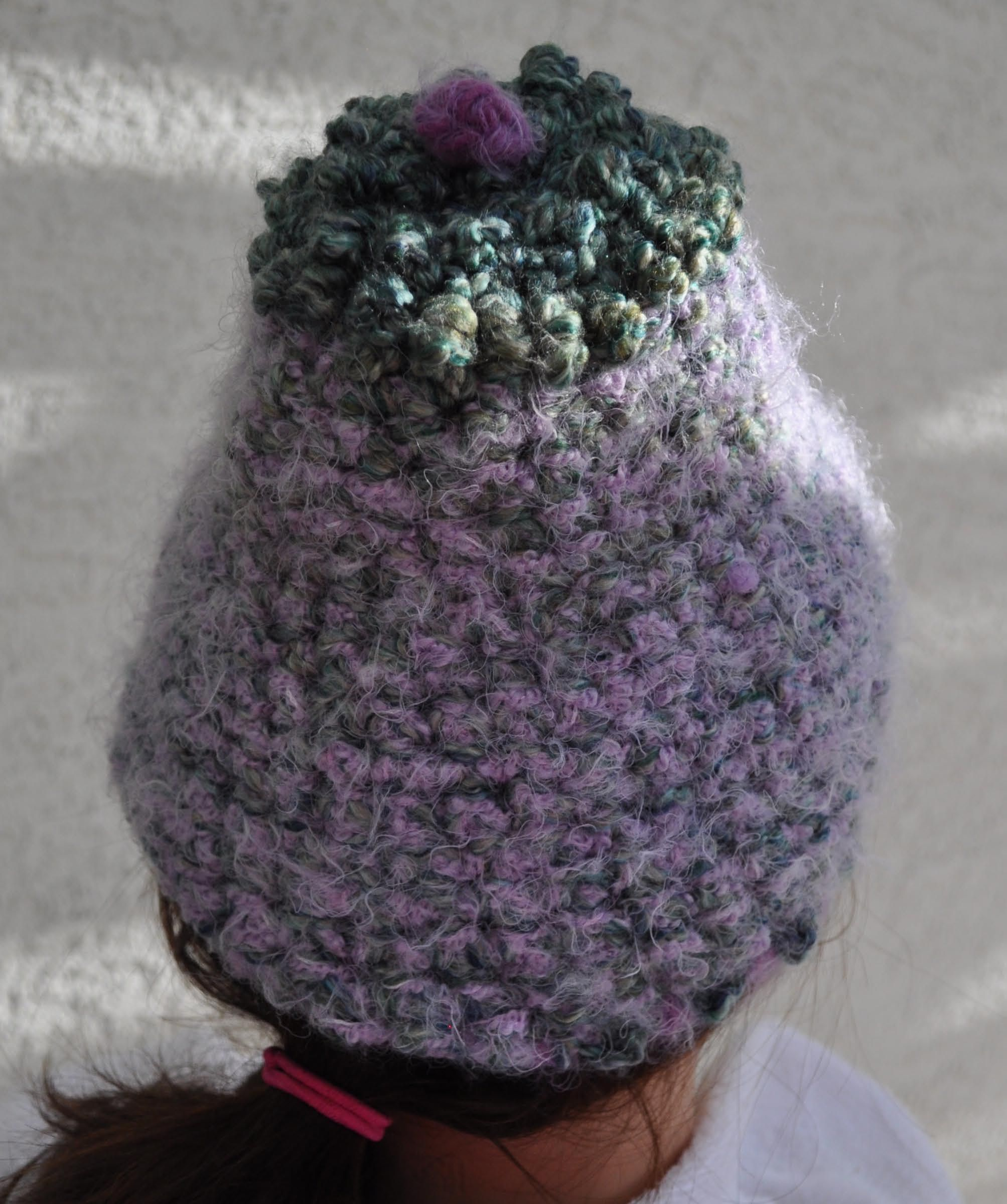 Heather pink and sage green yarn-crafted hat.