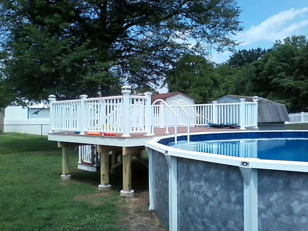 custom above ground pool decking with white vinyl railing and trex composite decking
