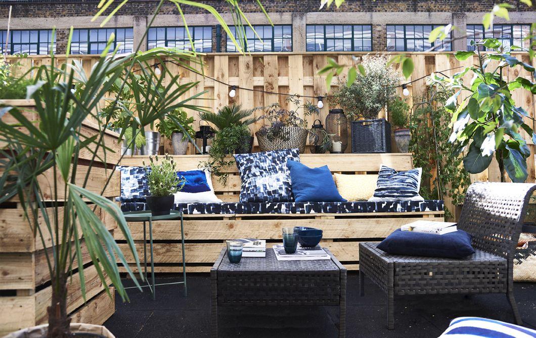 Kék párnák és kültéri bútorok egy teraszon.