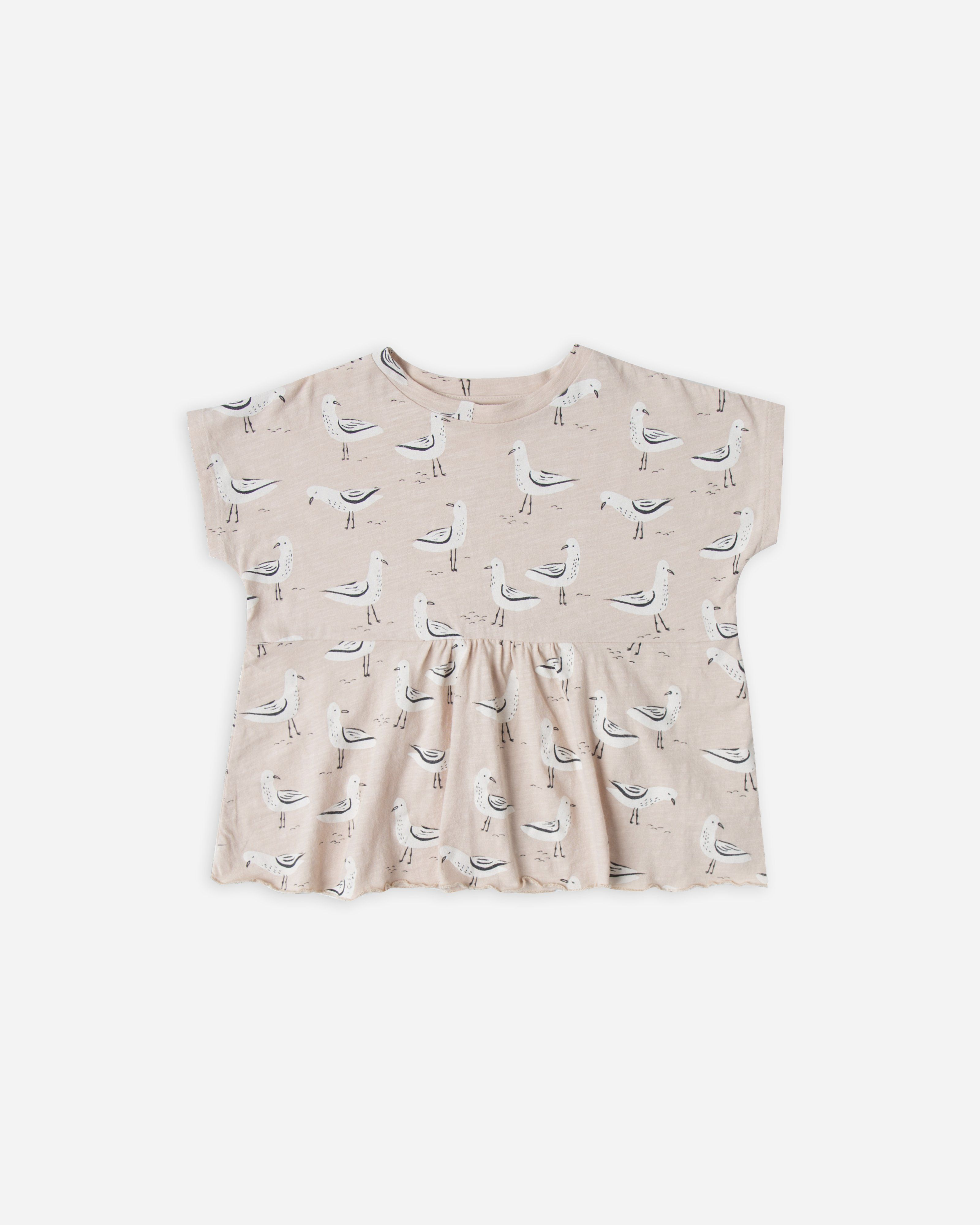 40a95150f1af Pearl colored top with seagull print. Short sleeves with gathered detail.  100% cotton