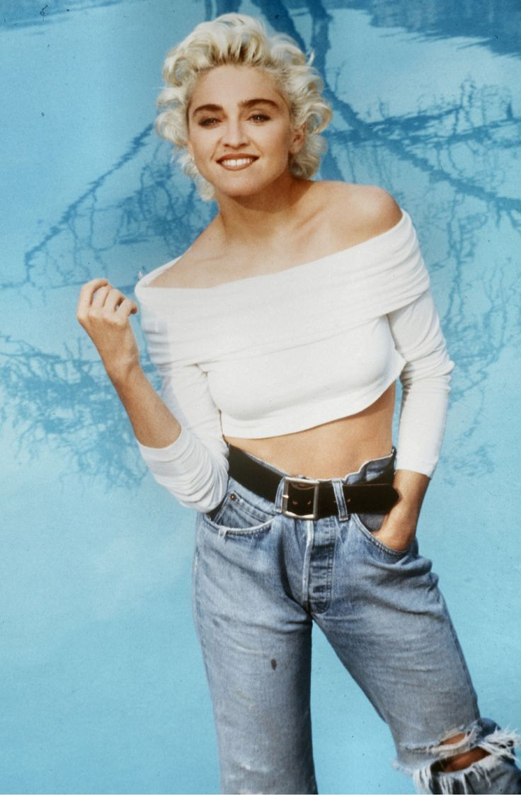 Madonna in high waisted ripped jeans cinched with a leather belt topped with an off the shoulder half blouse.