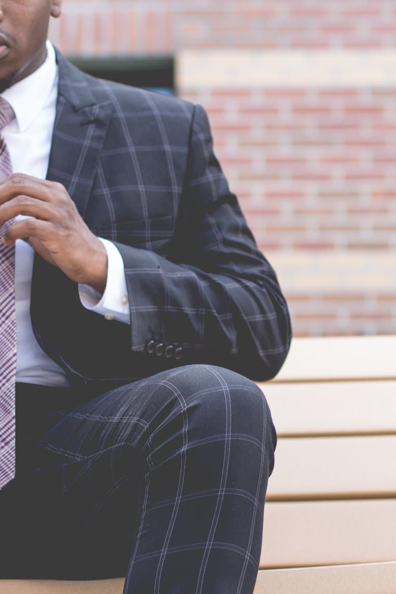 Man in Grey and Black Suit Jacket Sitting on Bench