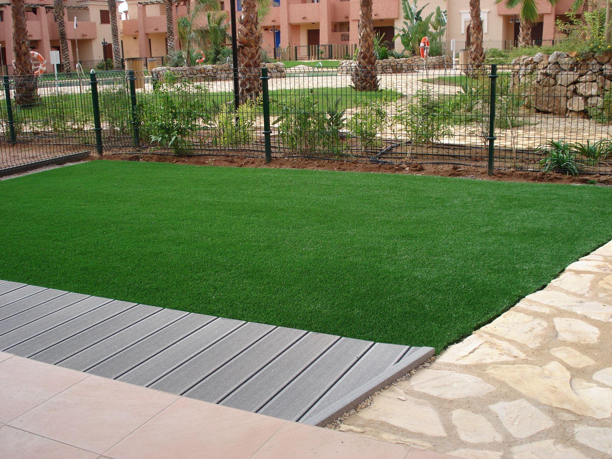 Jardin de un bajo con cesped artificil y tarima exterior for Piedras para patios exteriores