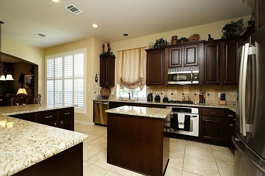 Dark Kitchen Cabinets With Light Granite Countertop And Backsplash