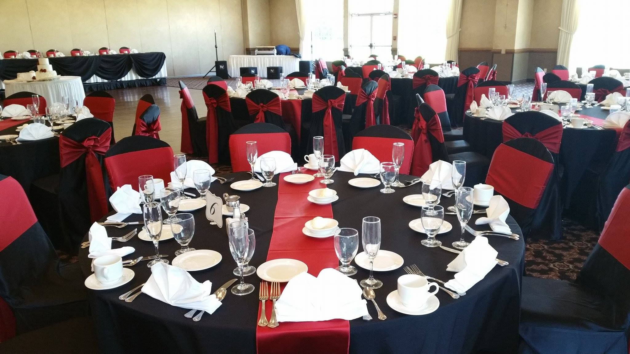 Black table cloths, deep red table runners and deep red satin sashes ...