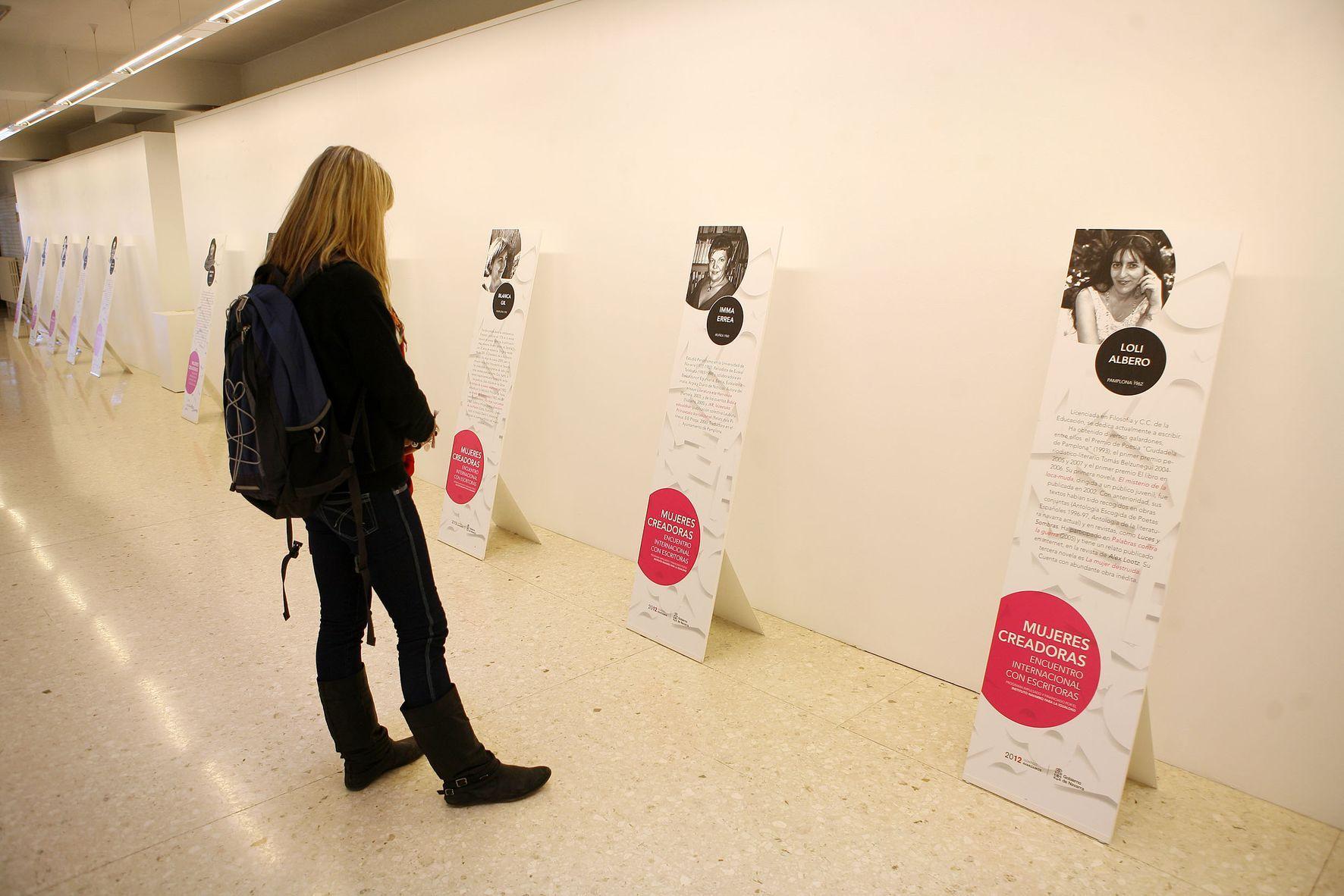 """Una mujer observa uno de los paneles de la exposición """"Escritoras de Navarra."""