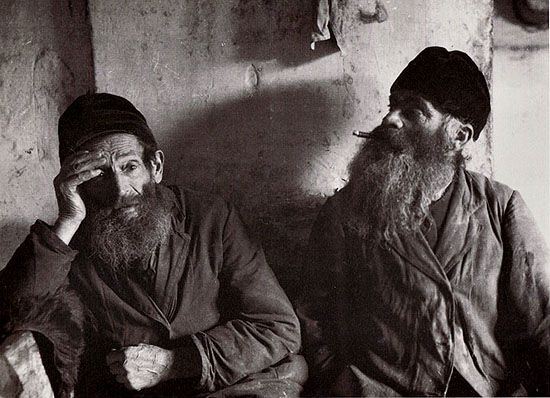 """""""Byale (Biała Podlaska, Lublin province), 1926. Father and son. To protect himself from the Evil One, Leyzer Bawół, the blacksmith, will not say how old he is, but he must be over one hundred. Now his son does the smithing and the old man has become a doctor. He sets broken arms and legs.""""  Photo by Alter Kacyzne."""