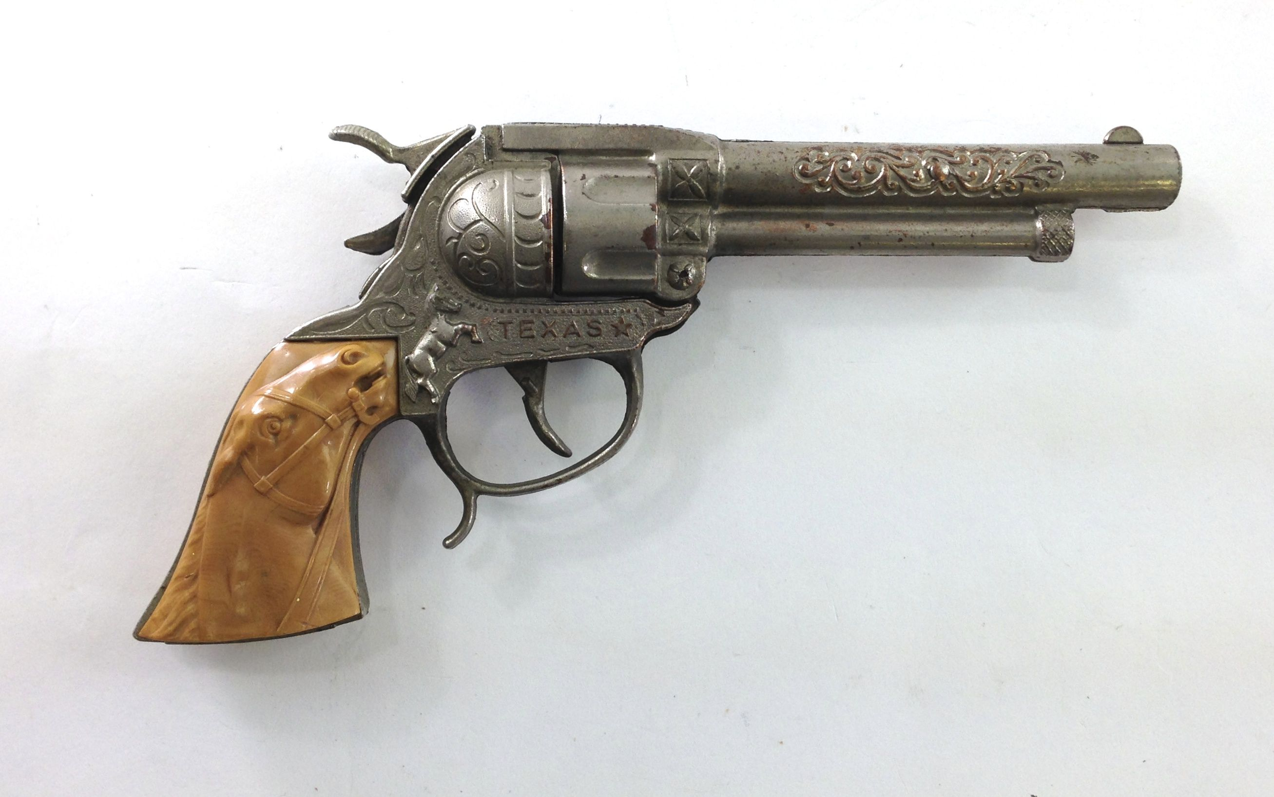 """This cast metal western style cap gunwas made in the 1950'sby Leslie Henry and is a """"Texas"""" model repeater cap pistol. Description from toygunslinger.com. I searched for this on bing.com/images"""