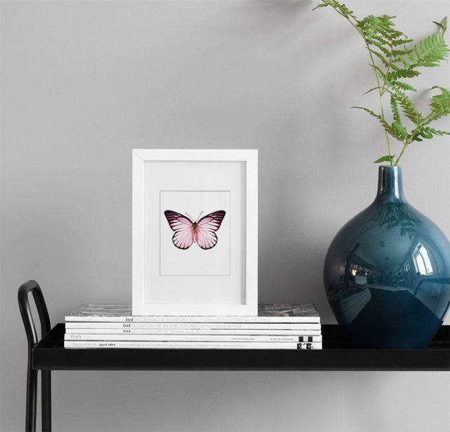 Juliste vaaleanpunaisella perhosella, tyylikäs osana sommitelmaa.