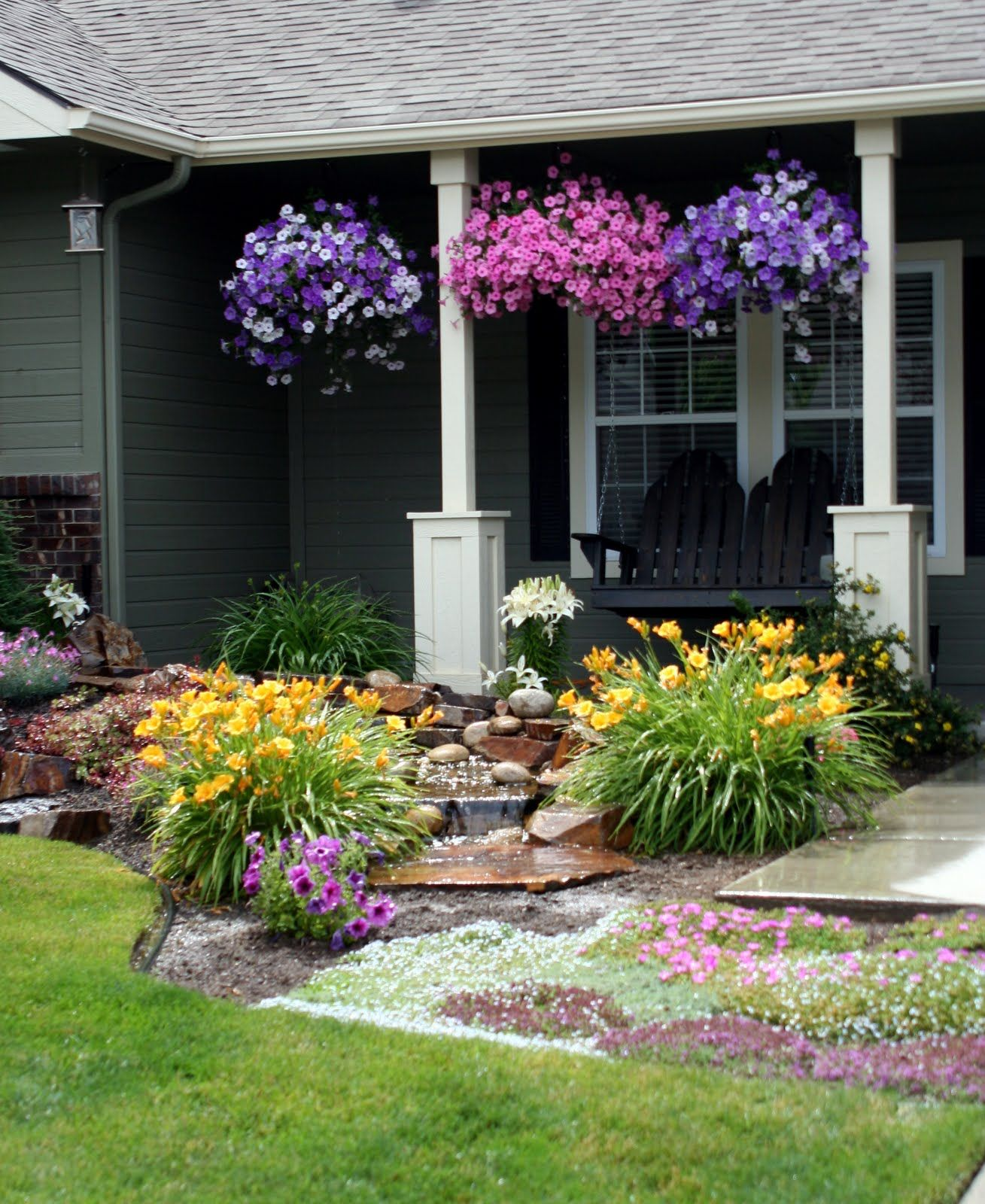 Front yard landscaping makeover with waterfall and adirondack porch swing.
