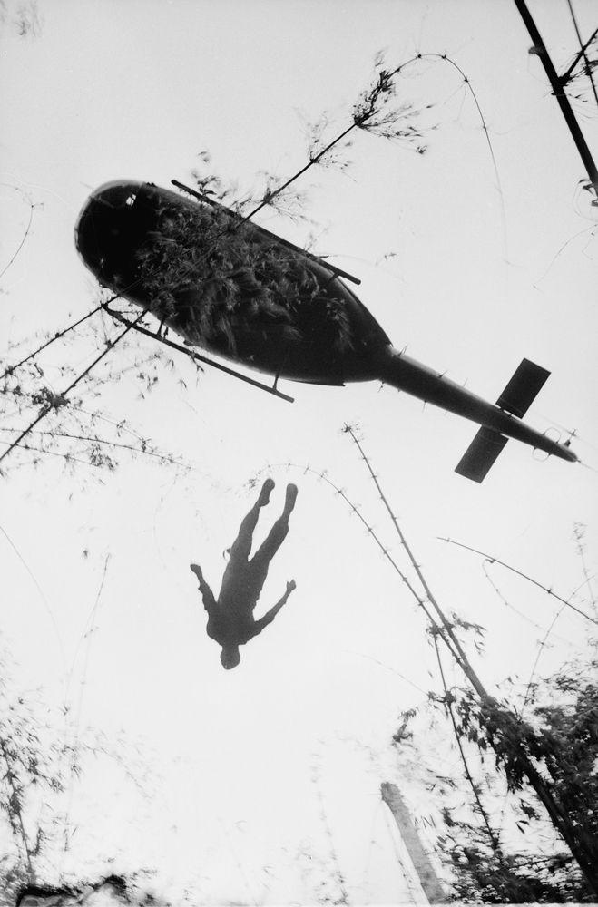 Il corpo di un paracadutista viene sollevato da un elicottero durante il trasferimento di una base al confine cambogiano, il 14 maggio 1966. - (Henri Huet, Ap/Ansa)