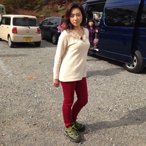 赤いパンツに白いニットを着て立っている藤吉久美子の画像