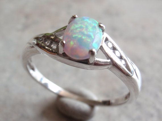 Lab created opal set in a size 11-1/4 sterling silver mounting with crystal CZ accents in very good vintage condition. It is marked 925 and has been