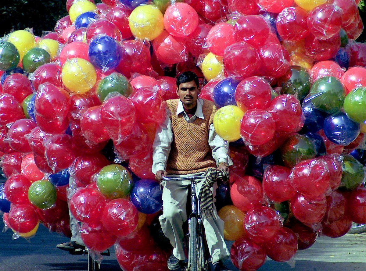 This man in India is biking around with a huge number of plastic balls.