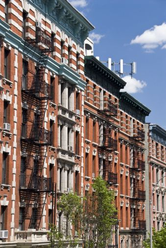 Colorful red brick apartments with fire escapes on West 125th Street ...