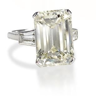 A diamond single-stone ring The step-cut diamond, weighing 7.46 carats, between tapered baguette-cut diamond shoulders