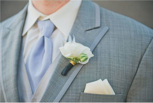 Elegant white floral boutonniere with black and gold wrap.