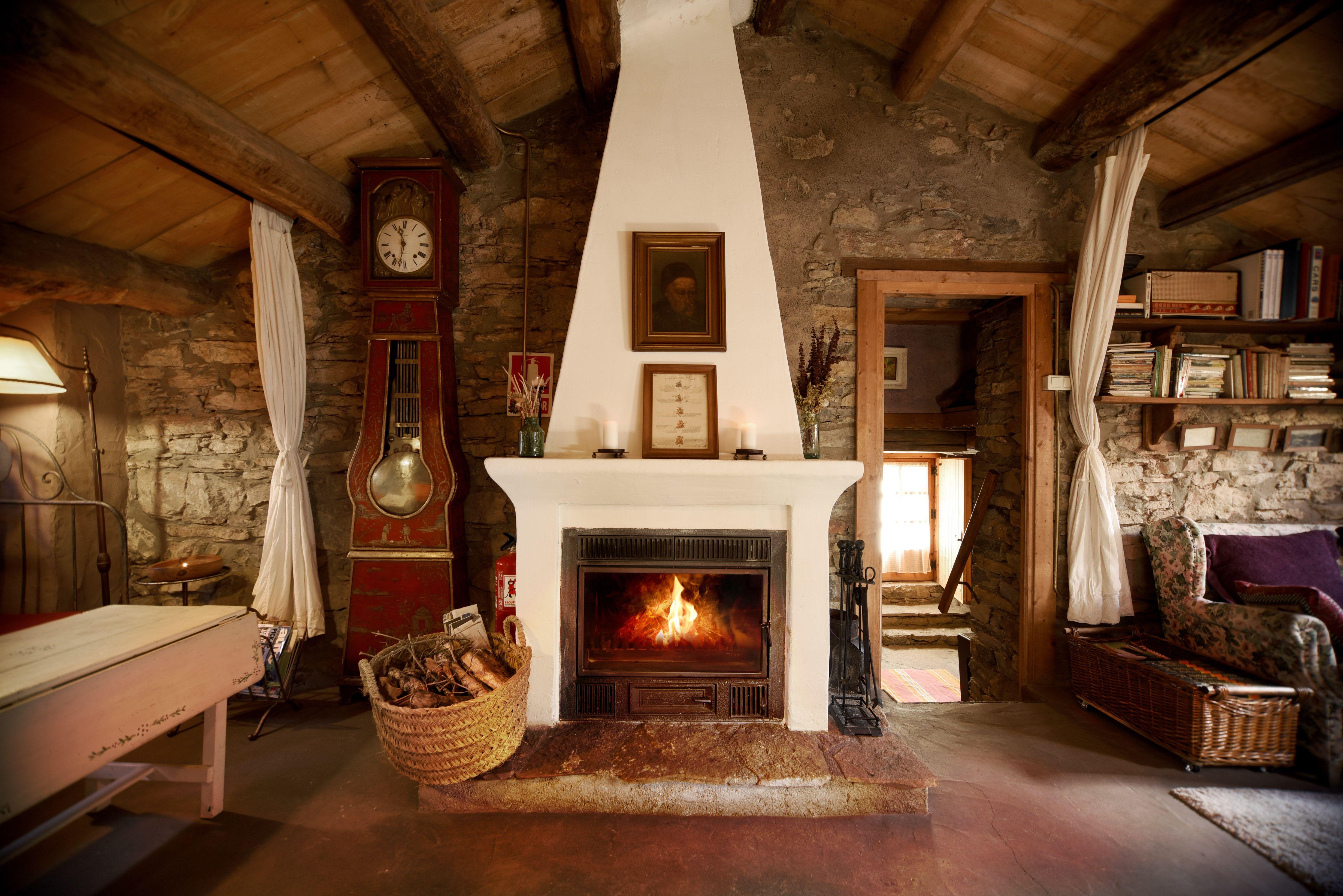 Sala de estar rústica, pared de piedra, techo de madera