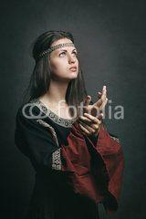 Beautiful woman in medieval dress praying
