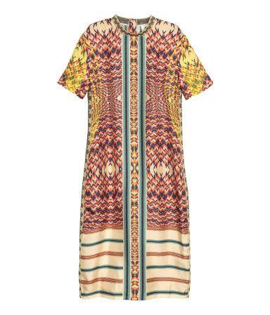 STUDIO COLLECTION/PREMIUM QUALITY. Knælang kjole i morbærsilke med trykt mønster. Kjolen er figursyet og har korte ærmer. Mønstret elastik i halsudskæringen og i sidesømmene. Skjult lynlås og slids bagpå. Uden for.