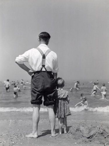 Strandleven. Volwassen man met wit overhemd, een broek met bretels en opgerolde pijpen, kijkt samen met een klein meisje naar volwassenen en kinderen die zich vermaken in de zee. Plaats en datum onbekend.