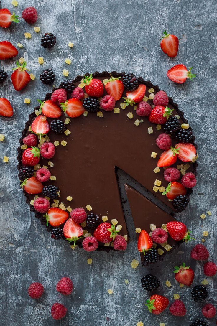 Top down photo of vegan chocolate ginger tart decorated with berries with a slice taken out. #combs
