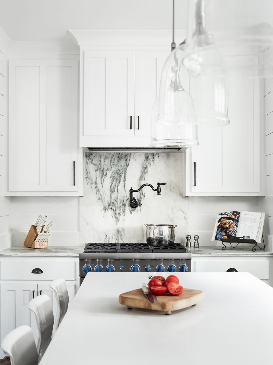 white kitchen with marble backsplash and glass pendant lights ...