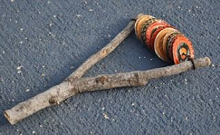 This would be an art project my kiddo could dig. Using a mallet to flatten the bottle caps, then some kind of terribly dangerous sharp object to pierce them (I would do that), then stringing them to the stick.