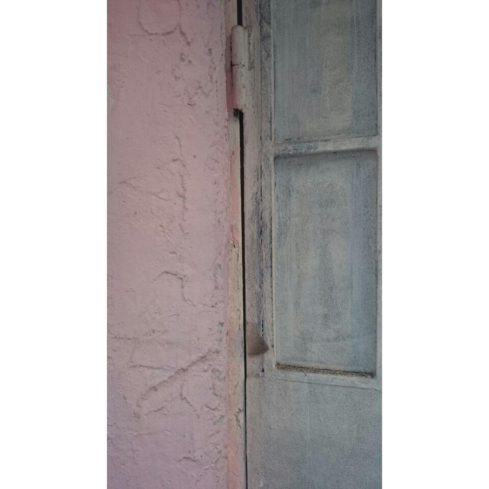 Postigo gris, pared rosa. En la calle antes de las nueve. Málaga. Fotografía Inmaculada Reina.