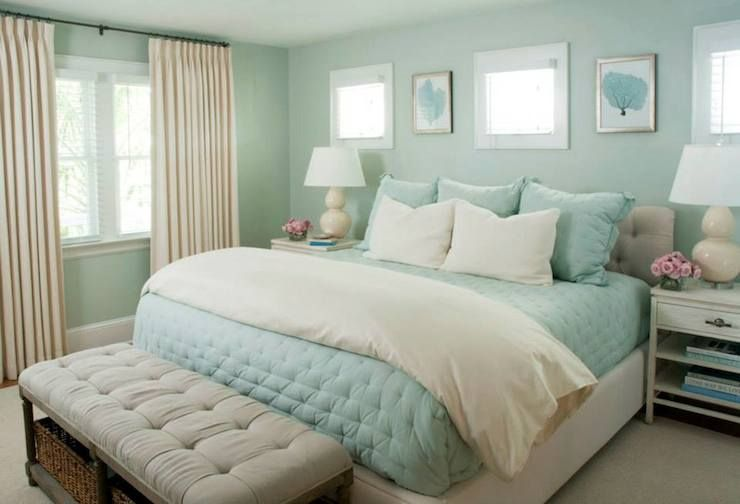 Chic Cottage Bedroom Features Framed Turquoise Seafans Flanked By Small Windows Over Light Beige Tufted Bed