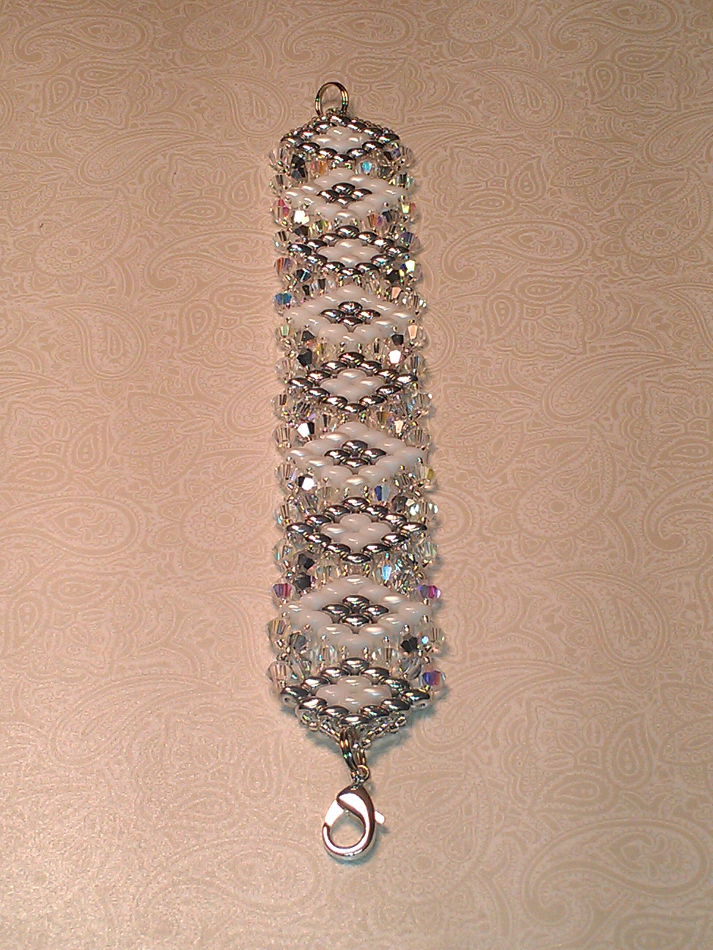 "A very big Thank You to  Aleshia from ""Beadifulnights"" youtube for a fantastic tutorial! ""Crystal Glitz"" bracelet in white and silver superduos with crystal ab and crystal argent flare 4mm bicones. I used crystal ab 11/0 Czech seed beads.  This pattern can be done in so many different ways. The photo does not really show how this one sparkles with all the beautiful crystals."