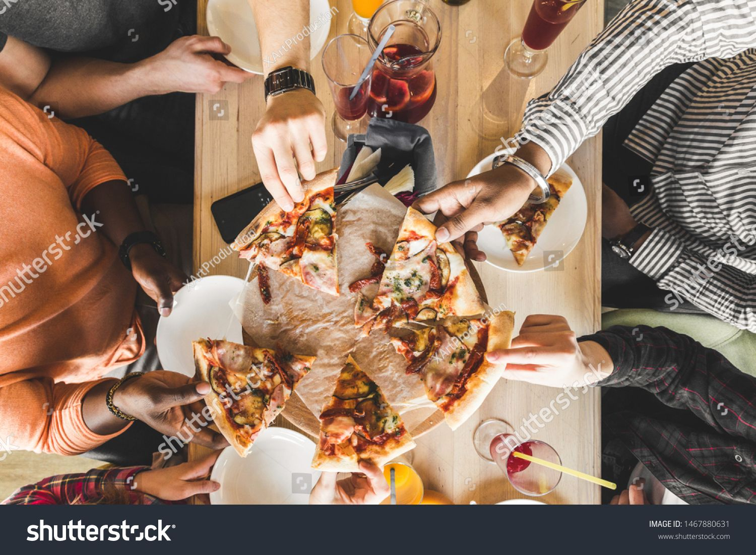 A company of multicultural young people in a cafe eating pizza, drinking cocktails, having fun #Sponsored , #ad, #people#cafe#young#company