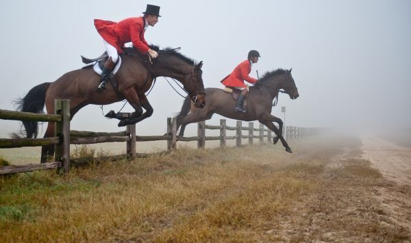 Riders Jump A Fence At Hobby Field As They Follow Their