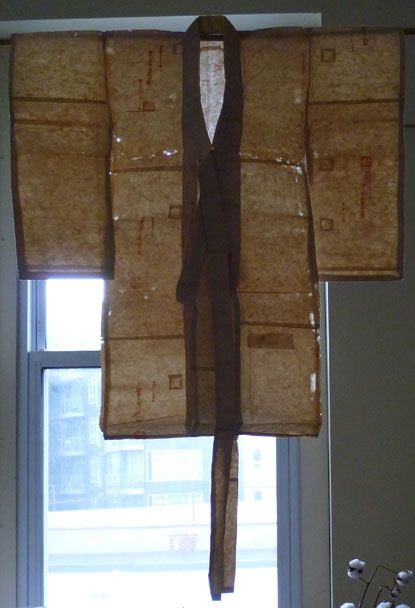 A Small Paper Hinagata: Backlit | It's a child's kimono rendered to size in repurposed ledger paper; the actual seams which construct the shape of the kimono are stitched, but the horizontal seams that you see in the backlit photo, are glued. via Sri Threads blog