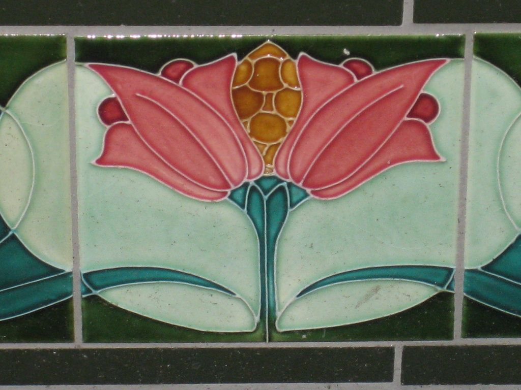 These beautiful stylised Art Nouveau flowers and leaves appear on a frieze of three tiles which feature in an Edwardian shop front along Sydney Road in the Melbourne suburb of Coburg. Barely noticed as they are situated very low to the ground, in spite of their vibrant colour, they are lucky enough to have survived unscathed throughout the ensuing decades and have not been torn down by developers re-fitting the shop.