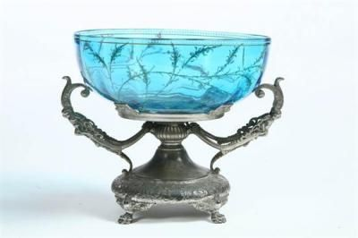 "BRIDE'S BOWL WITH SILVER PLATED BASE. Blue bowl with enamel beaded rim and interior gilt and berry decoration. Rests on an ornate silver plated base with cherub handles signed Wilcox. 8 1/4"" h. 9"" dia."