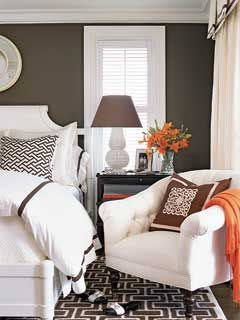 slaapkamer [In this guest bedroom, bold brown-and-white geometric prints unify the space. Bright, white fabrics as bed linens, curtains, and chair upholstery lighten up the dark brown wall paint. Accent the space with bold geometric throw pillows and a fun colored blanket.    --Coastal Living, designer Dominique Vomillon]