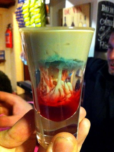 Zombie Shot  Here's how you make one:  Fill a shot glass halfway with peach schnapps  Gently pour Bailey's Irish Cream on top  After the shot is almost full, carefully add a small amount of blue curacao   After it settles, add a small splash (or a few drops) of grenadine syrup.  BOOM zombie goodness