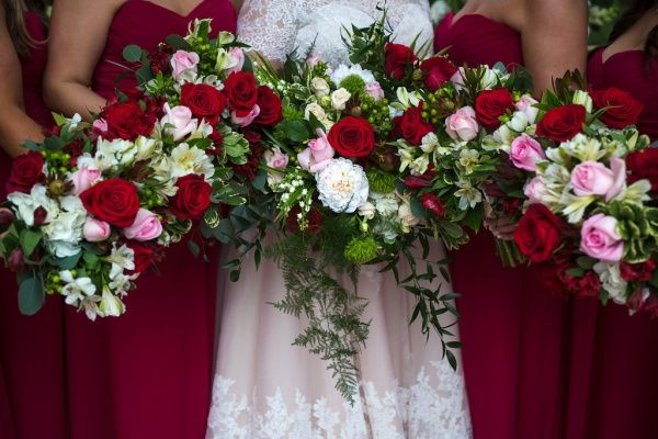 Gorgeous, deep red bouquets with a touch of pink!  Taken at THE SPRINGS in Norman by Hailey Faria Photography.