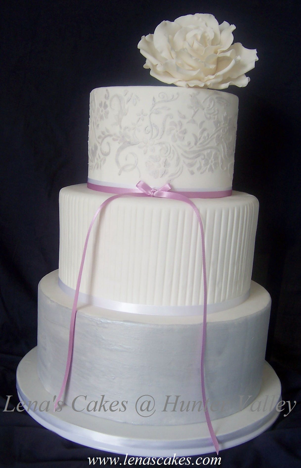 3-tier wedding cake. Silver, white and light purple. Topped with ...